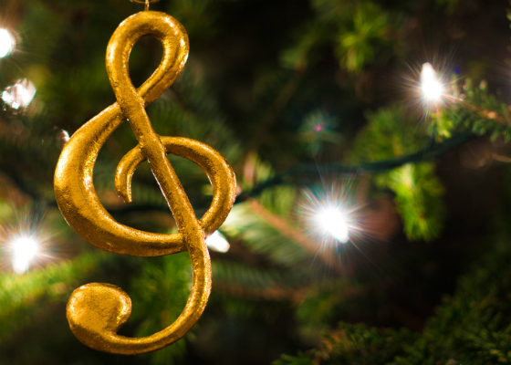 A musical note decoration hanging from a Christmas tree